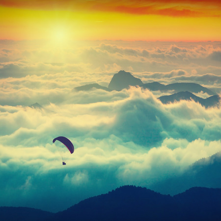paraglide: Paraglide silhouette over mountain peaks. Sunrise in a high mountains foggy valley of Crimea Ukraine