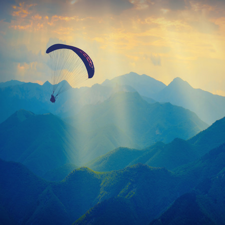paraglide: Paraglide silhouette flying over the mountain peaks. Beautiful rays of light in a high mountain valley.