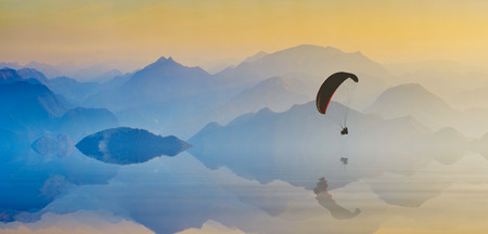paraglide: Paraglide silhouette over the mountain lake reflected in water