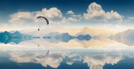 paraglide: Flying paraglide silhouette over the extensive smooth water surface of a mountain lake reflected in water Stock Photo