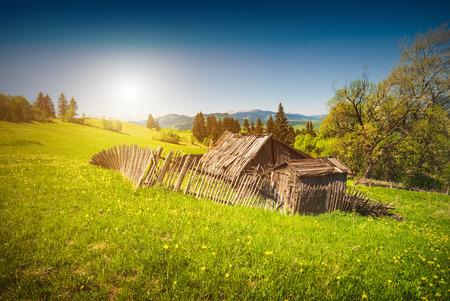rundown: Sunrise in a spring village with broken old woden house in a valley.