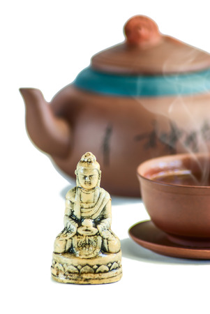 Buddhas figure with teahouse and green tea in a teacup isolated on a white background