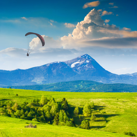 paraglide: Paraglide silhouette flying over Carpathian spring mountain valley. Majestic landscape with beautiful red clouds above the high mountains