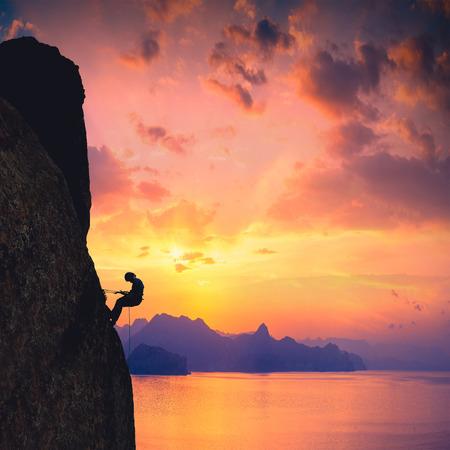 stijger: Silhouet van bergbeklimmer tegen zonsondergang over de zee achtergrond
