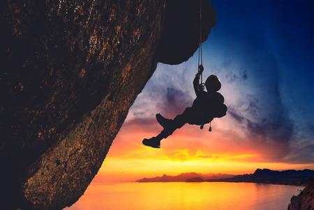 Silhouette de grimpeur de roche escalade une falaise en surplomb avec coucher de soleil sur le coucher de soleil sur un fond de la mer Banque d'images - 40931451