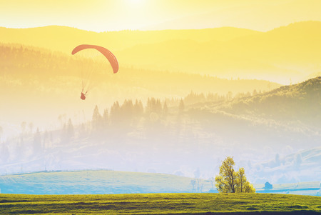 paraglide: Paraglide silhouette flying over misty mountain valley in a warm light of sunrise. Stock Photo