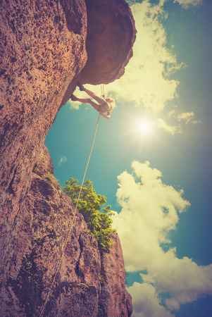 belay: Rock climber against the sky background. Vintage colors Stock Photo