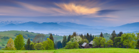 Early morning in a Carpathian mountain valley with beautiful moving clouds in a sky