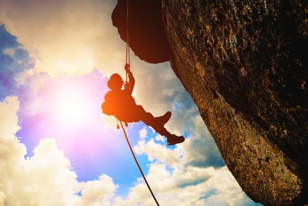climbing: Silueta del escalador de roca contra el fondo del cielo puesta de sol Foto de archivo