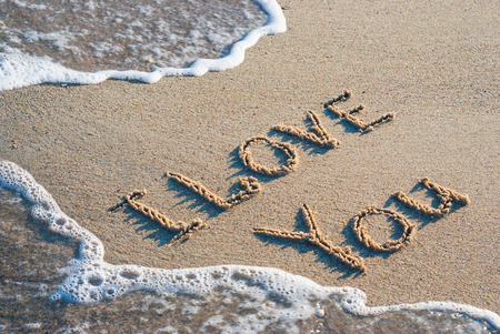 infatuation: words I love youwritten on the wet sand beach with the wave
