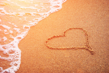 Heart drawn in the sand of sea beach