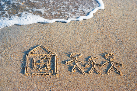 Family of three people with little house drawn in the sand of sea beach