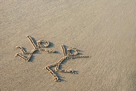 agradecimiento: Dos personas felices de salto dibujados en la arena de la playa del mar Foto de archivo