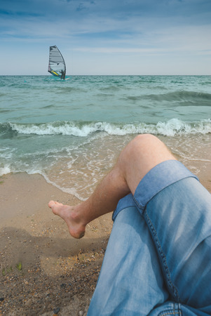 windsurfers: Man with legs in sand sitting on a sea beach and enjoy windsurfers swimming Stock Photo