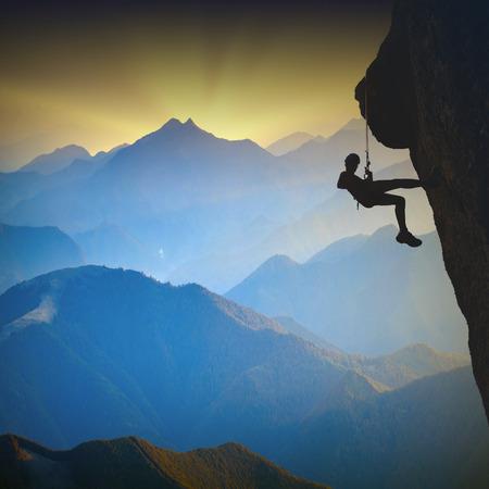 안개 낀 산 계곡에 대한 절벽에 산악인의 실루엣 스톡 콘텐츠