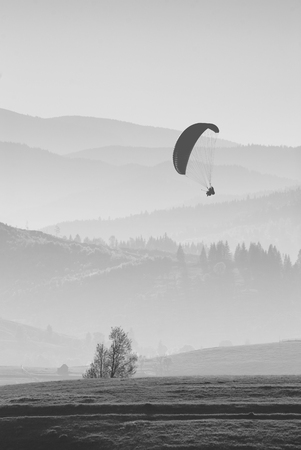paraglide: Paraglide silhouette flying over misty mountain valley in a light of sunrise. Monochrome colors Stock Photo
