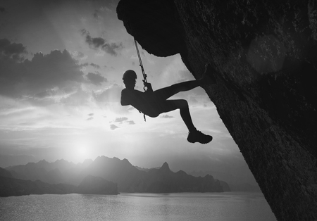 trust: Silhouette of climber on a cliff against beautiful sunset above the sea. Black and white