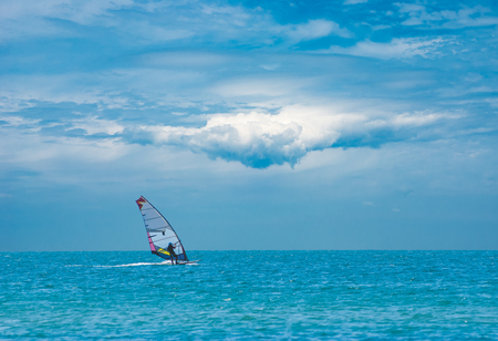 wide  wet: Alone surfer on board in sea with beautiful clouds in a sky