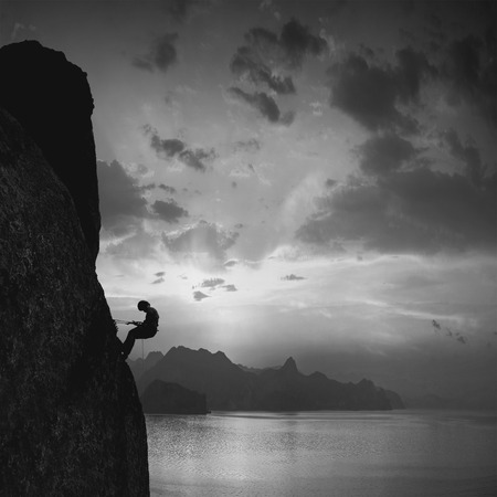 nature silhouette: Silhouette of rock climber against sunset over the sea background. Monochrome