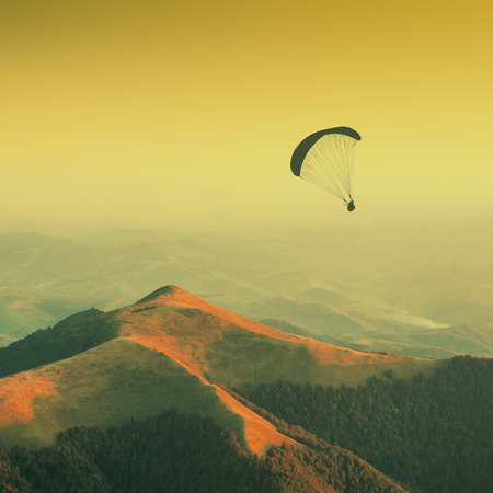 paraglide: Paraglide silhouette in a light of sunrise above the misty valley. Warm vintage colors