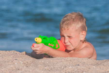 water gun: Little boy play with water gun on a sand beach of Black sea