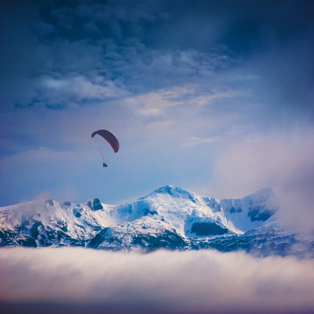 paraglide: Paraglide silhouette in a light of sunrise above the snow-capped peaks of winter mountains
