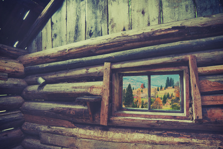 workhouse: View from window of rustic wooden house to Carpathian mountain village. Ethnic cottage. Vintage colors Stock Photo