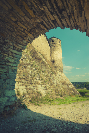 middleages: View through the stone arch to the ancient castle. Sepia stylisation. Europe, Ukraine