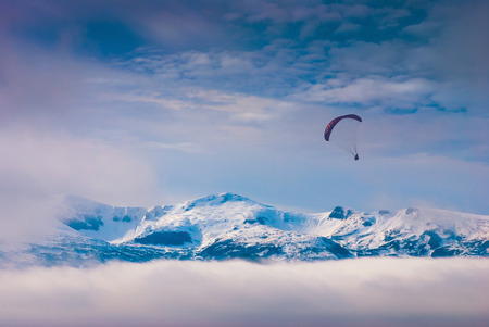 paraglide: Paraglide silhouette in a light of sunrise above the snow-capped peaks of Carpathian winter mountains