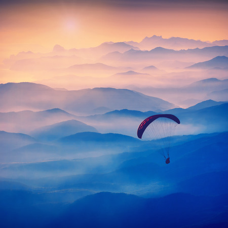 paraglide: Paraglide silhouette in a light of sunrise above the misty Crimea valley. Vintage colors