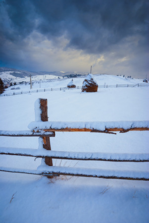 sheepfold: Carpathian winter valley with haystacks covered with fresh show Stock Photo
