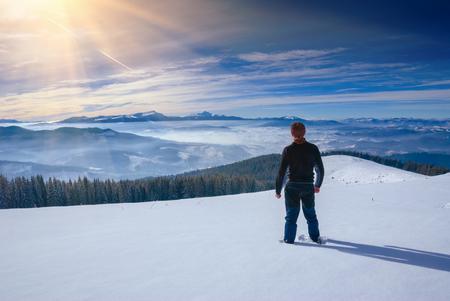 stays: Hiker stays in a Carpathian mountain valley and enjoy winter landscape. Ukraine, Europe