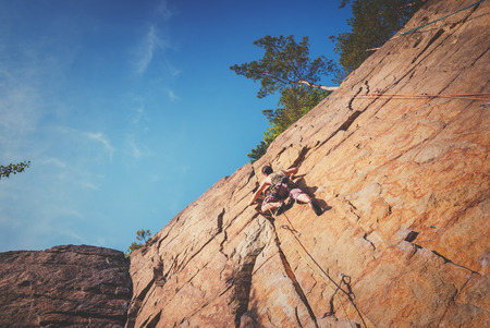 rock stone: Young strong man climbs on a yellow cliff to the blue sky Stock Photo