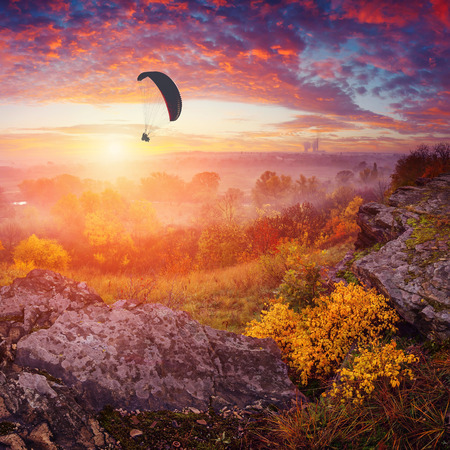 paraglide: Paraglide in a sky above the misty valley. Wonderful bright colorful sunrise with beautiful red clouds.