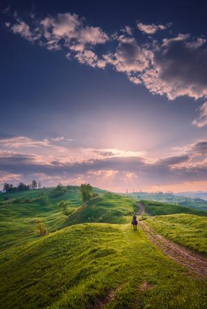 uomo a cavallo: Majestic alba primavera in una valle di montagna dei Carpazi con belle slouds in un cielo. cavaliere solitario su un prato verde.