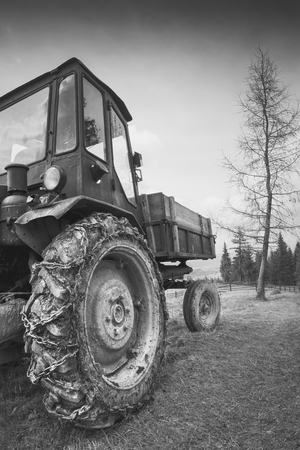 mini loader: Old rustic Soviet tractor in a Carpathian mountain valley. Big dirty wheel in a chain. Monochrome colors
