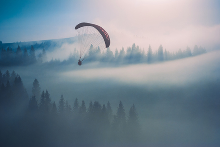 paraglide: Paraglide silhouette flying over misty mountain valley