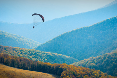 paraglide: Silhouette of flying paraglide in a sky above the misty autumn valley.