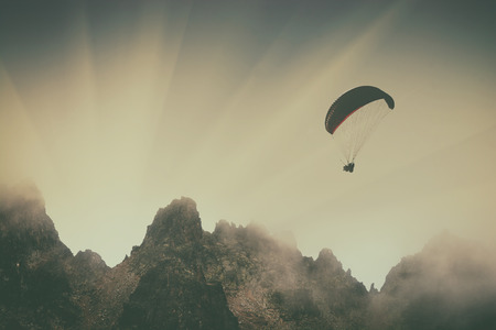 paraglide: Silhouette of paraglide flying over the caucasian rocky misty mountains in a light of sunset. Georgia, Svaneti region. Vintage colors.