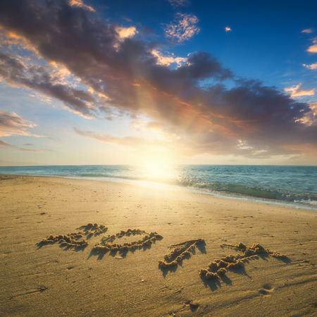 Year 2017 written in sand on a sea beach. Majestic sunrise with beautiful clouds in a sky. Stock Photo