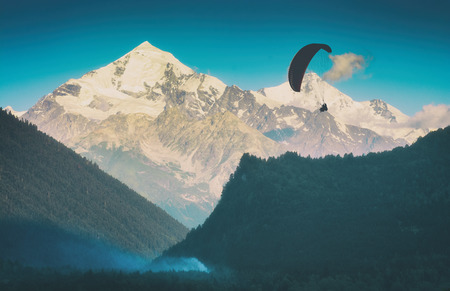 Silhouette of paraglide flying over the caucasian high mountain valley. Georgia, Svaneti region.