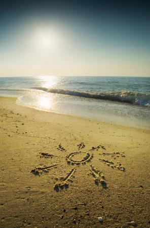 orthographic symbol: Symbol of sun written on a sand beach. Beautiful sunrise above the sea.