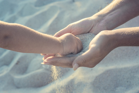 pass away: Mother and small baby play with sand. Baby take some sand from mothers arms. Active parents and people outdoor activity on summer vacations with children.