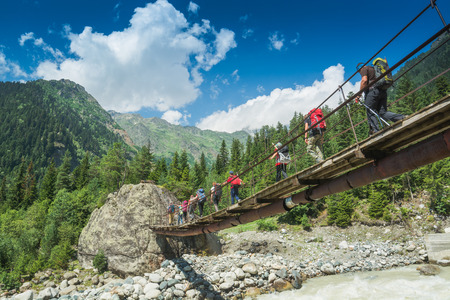 svaneti: Group of hikers with backpacks go on a suspension bridge over the mountain river. Caucasian mountains, Georgia, Svaneti region.