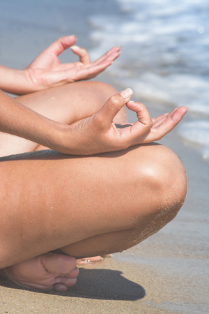 Woman relaxing by practicing yoga on the sea beach, close-up of hands, gyan mudra and lotus position Stock Photo