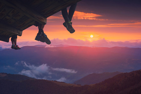 plafond: Hikers sit on a wooden flooring above the mountain valley and enjoy sunset.