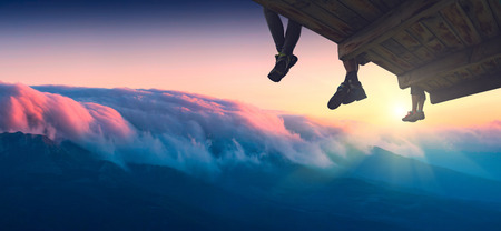 plafond: Hikers sit on a wooden flooring above the mountain valley and enjoy majestic sunrise.