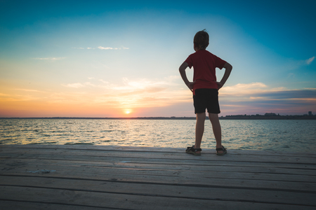 stays: Little boy stays on a pier and enjoy sunset on a sea.