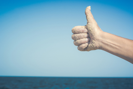 confirmed: Close-up picture of womans hand on the beach against blue sea Hand showing thumbs up or shows good and like. Stock Photo