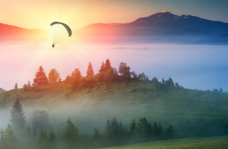 paraglide: Paraglide silhouette flying above misty carpathian hills against majestic sunrise in a mountain valley Stock Photo